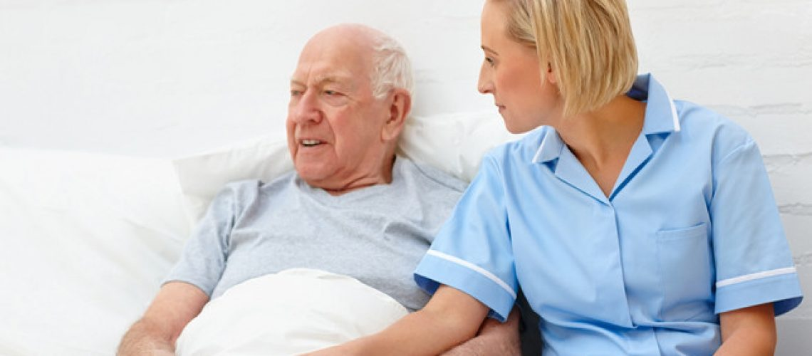 Caring healthcare worker consoling elderly patient in care home